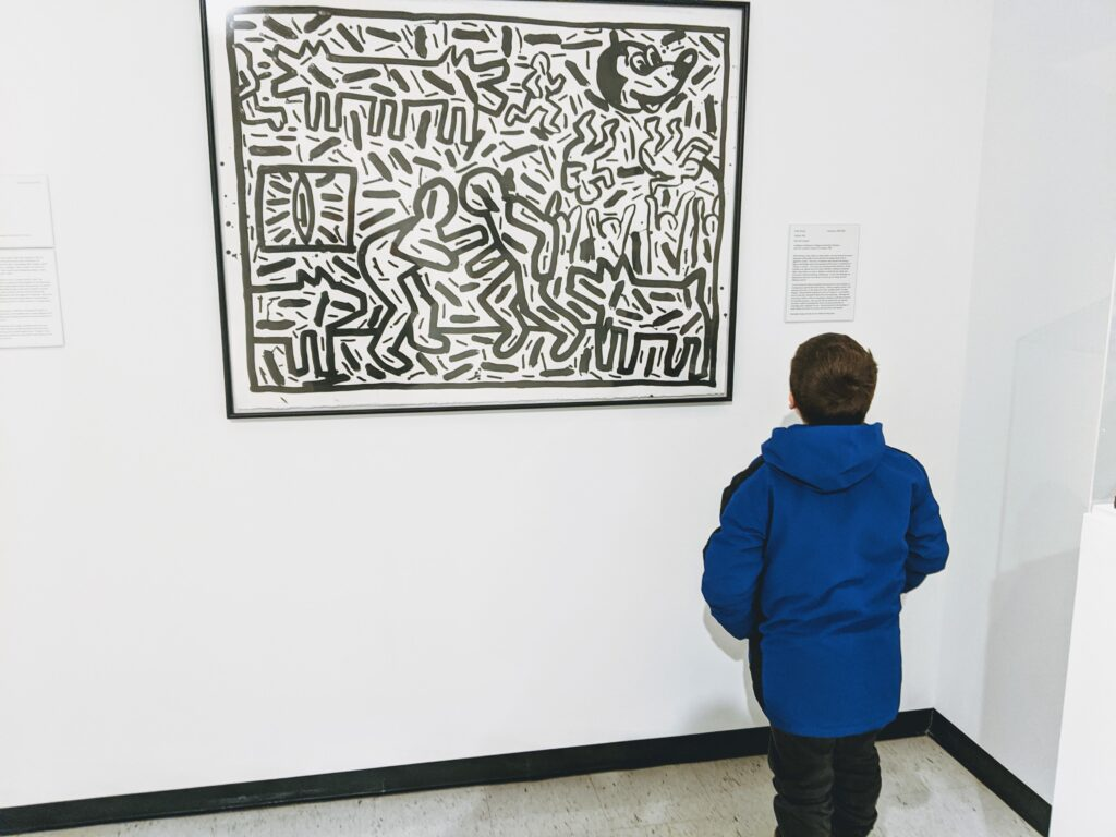 Kid standing in front of Keith Haring painting