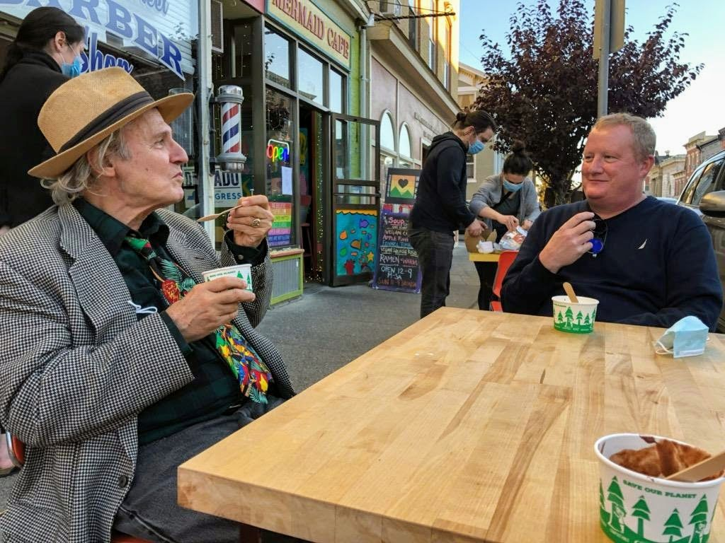 Two men eating ice cream at a sidewalk cafe